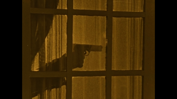 Still from the film Secrets of the Night - gun behind a curtain
